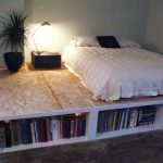 Lightwood Platform Bed With Bookshelves Underneath Black Bedside Table With Modern Table Lamp A Black Plastic Pot With Decorative Plants