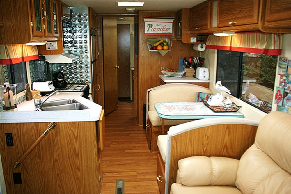 Lounge of RV with a pair of long chairs with table a small corner preparing  table