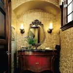 Luxurious Classic Powder Room With Classic Wood Vanity With Sink And Dark Stained Bronze Faucet Classic Oval Mirror A Pair Of Vanity Light Fixtures Gold Tone Wallpaper With Floral Pattern