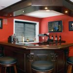 Luxurious small wine bar in basement with ceiling lamps black window blinds a flat TV set two picture frames some bottles of wine and leather wrapped barstools