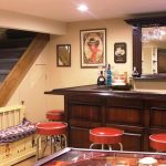 Mini wine bar in basement with red barstools some wall decorations a decorative mirror for bar staircase