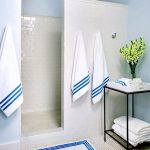 Minimalist shower room without door with pure white tiles wall system and crate for towels and decorative items