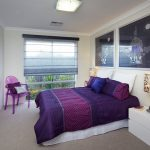 Modern bedroom decor idea with purple bedding and pillows a purple corner chair with pillows glass window with semi transparent shade a pair of minimalist white bedside tables with table lamps