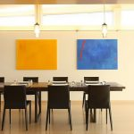 Modern dining room idea with attractive color tones of yellow red and blue two modern pendant lamps a set of dining furniture with large table for eight dining chairs