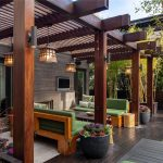 Modern home deck cover design green sofas with black table big wooden pillars some spot light fixtures installed on each pillar beautiful pendant lamps for outdoor black stained wood planks flooring