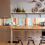 Modern kitchen design with colorful backsplash gloss wooden kitchen countertop a long floating shelf for displaying decorative pieces unique pendant lamp gloss wooden table with three bartsools