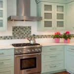 Mosaic backsplash tiles idea for country kitchen design white kitchen counter light turquoise kitchen cabinetry a pair of beautiful pink pots with plants dark stained wood floors