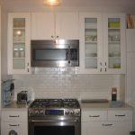 Most common white ceramic subway tiles backsplash in kitchen modern gas stove appliance  ceramic counter in cream color white painted storage system for kitchen