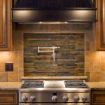 Natural tone backsplash tiles for kitchen in country style with brown granite kitchen countertop wooden kitchen cabinets and large gas stove