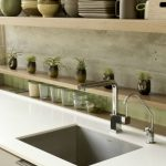 Original and plain concrete backsplash with some small decorative pots for decorative plants white countertops with square sink and double stainless steel faucets open shelf for storing dishware