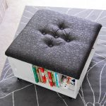 Ottoman with book shelf underneath and textured black leather top and also wheels