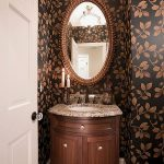 Powder room design with small vanity with sunk and brushed bronze faucet a pair of candle stands marble countertop oval decorative mirror and wallpaper with flower motifs