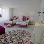 Round bedroom rug with beautiful colorful flowers patterns a pair of single bed furniture with heart shaped headboard a daybed in pink a standing lamp a vanity organization with mirror white lace curtain