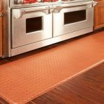 Rubber kitchen rug in red color dark brown stained wood planks floors