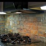 Rustic kitchen backsplash idea a gas stove light fixtures under cabinetry