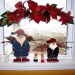 Santa Clause miniatures and cute baby miniature plus red flower arrangement as Christmas decorations for windows