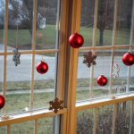 Simple Christmas decorations idea for windows consisting of red Christmas balls and metal ornamental feature