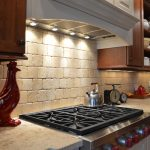 Simple rustic backsplash in lighter cream color gas stove some recessed light fixtures under kitchen cabinets