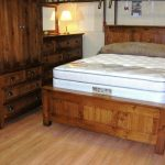 Simple Rustic Style Bedroom With Wood Bed Furniture With Higher Headboard Large Storage System Made Of Hardwood A Table Lamp White Wallpaper Unfinished Floor System