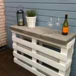 Simple small wine bar idea with white painted wood structure a pair of wine glasses a wine bottle a white decorative pot and plants