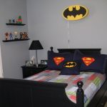 Simple superhero bedroom with Batman's and Superman's symbols applied on pillow covers black shelves for organizing the miniature of superhero black paint bedside table with black table lamp