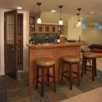 Small corner wine bar in basement with three barstools and four small pendant lamps