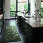 Small green kitchen rug with simple pattern black wood planks floors system a luxurious kitchen island with black storage system granite surface square deep sink and faucet