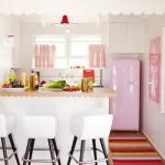 Small kitchen with cute decoration such as pink covered refrigerator pink window curtains a kitchen island with wooden top and white barstools rainbow mat wood floors