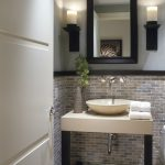 Small Powder Room In Simple Design With Half Way Brick Wall System A Pair Of Vanity Lighting Fixtures Black Wood Framed Mirror Simple Vanity With Sink And Wall Mount Faucet Two Rolls Of White Towels