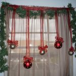 Some hanging Christmas ball ornaments in red and silver colors green artificial grass framing the glass window that is covered with light brown lace curtain