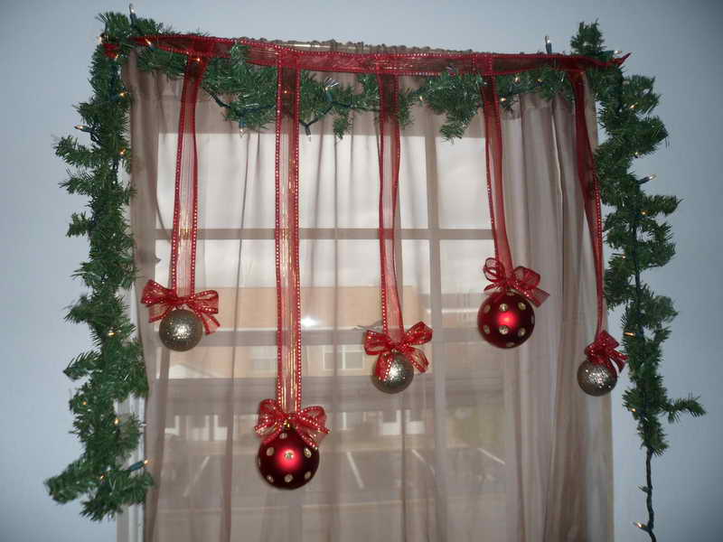 some hanging christmas ball ornaments in red and silver colors green artificial grass framing the glass