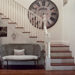Super huge clock as wall art installed on wall near staircase white painted wood handrail and railing system of the stair a classic sofa with a throw pillow