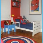 Superhero bedroom idea with small bed furniture a rounded rug with Captain Of America theme small bedside table in blue color large Spiderman painting as wall decoration floating black wood shelves