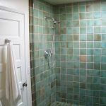 Turquoise tiles wall system and floor system for doorless shower space with wall mount showerhead and a heldhand showerhead