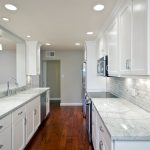 White and light grey subway ceramic tiles backsplash white marble kitchen countertop white kitchen cabinets electric stove white kitchen sink and faucet  wood planks floor idea