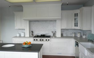 White kitchen backsplash modern gas stove white kitchen cabinet systems white countertop white sink and faucet a kitchen island with dark grey top darker stained wood floors