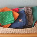 a basket of cloth napkin design in colorful style with various pattern of polka dot and chevron on wooden floor