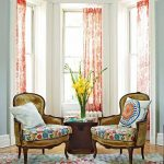 a pair of throw pillows with white cover base plus classic motifs a pair of corner chairs beautiful rug with colorful flower motifs red windows curtains