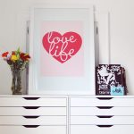 adorable white flat file cabinet from ikea with unique and lovable pink heart shape decoration with flower vas and photo