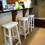 adorable white  upholstered bar stool design with footrest beneath bar table with table ware in creamy room with artistic decoration