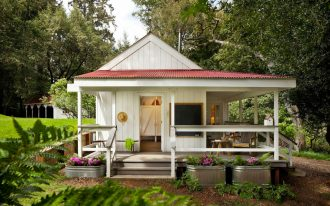 adorable white wooden pier and beam house plan idea with red roof and grassy meadow and fertil tree and natural ground
