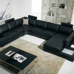 affordable black leather sectional couches with black glass top coffe table and wooden backcase and stylish lamp shade and soft rug