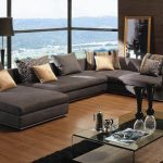 affordable sectional couches in grey with decorative cushion and glass coffe table on top of black rug and wooden laminate floor plus bookcase and standing lamp