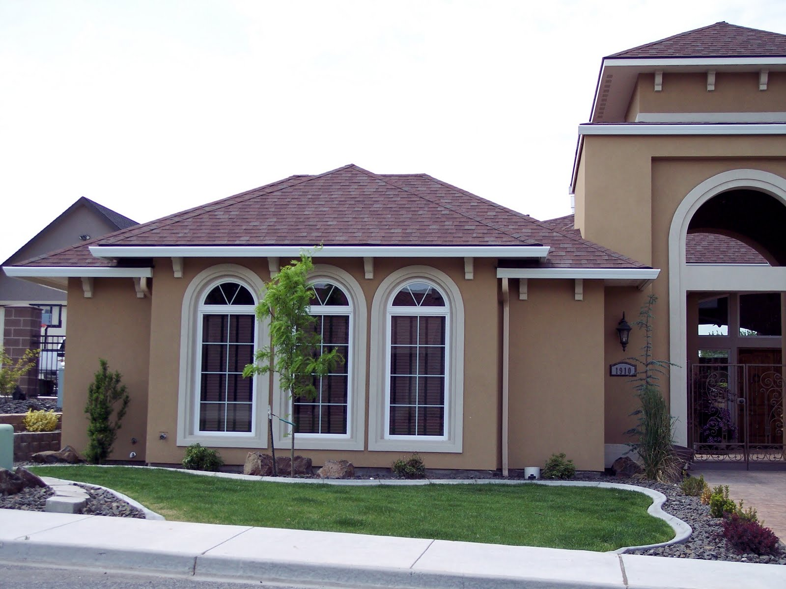 Architectural House Design With Brown Roof And Arched White Window With Bar  And Green Landscape And