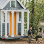 astonishing small mobile home that looks like house with gray wall and orange door with transparent window aside like