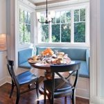 bay windows with built in sofa in blue color round wood table with a pair of black chairs a classic pendant lamp darker staining wood floors