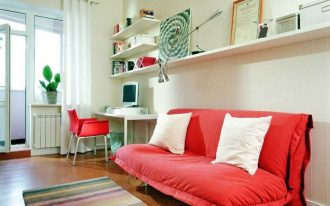 beautiful and comfortable soft red sofa that turn into bed design with white cushions beneath wall storage above rainbow colored area rug aside working station