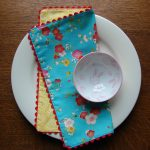 beautiful blue with yellow background with floral pattern napkin cloth design on white plate with mall cup