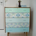 beautiful bohemian retro dresser design bathed in blue color with floral pattern accent with wooden legs beneath white wall with vas decoration