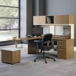 beige modular office computer desk with black swivel chair in grey office design with glass window